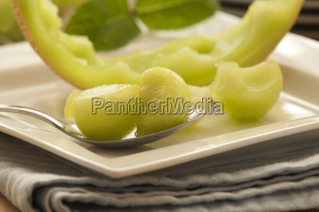 plate of honeydew melon with spoon