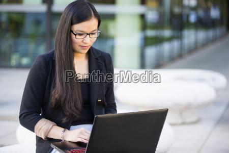 junge geschaeftsfrau die laptop verwendet