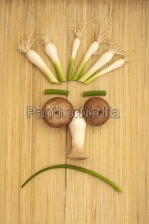 trauriges gemuesegesicht mit pilzen fruehlingszwiebeln und