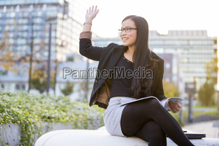 junge geschaeftsfrau mit zeitschrift gruss jemand