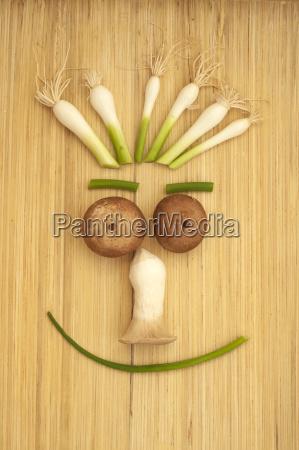 glueckliches gemuesegesicht mit pilzen fruehlingszwiebeln und