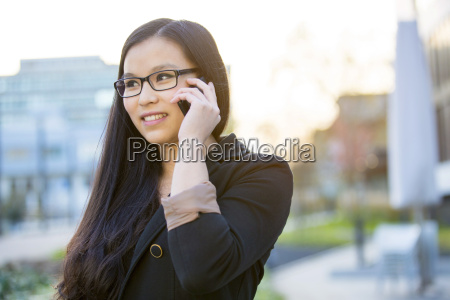 portrait of young businesswoman telephoning with