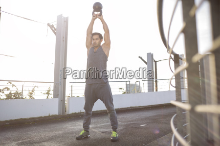 man training with kettlebell at backlight