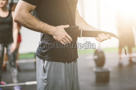 athlete in gym putting on weightlifting