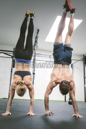 couple in gym training handstands