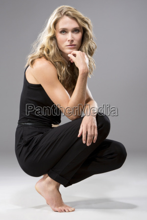 portrait of crouching woman wearing black
