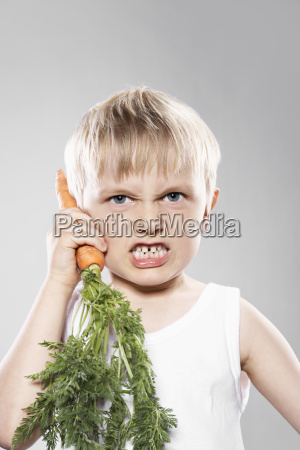boy imitating carrot as telephone close