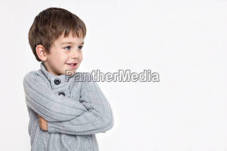 boy standing against white background smiling