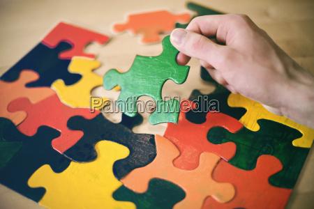 hand haelt ein grosses puzzleteil auf