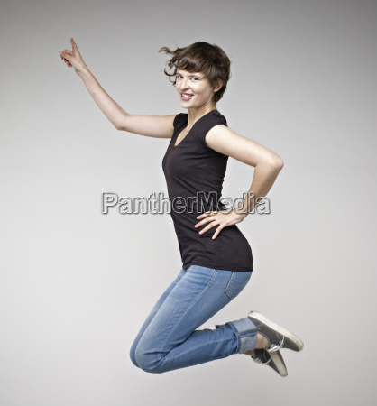 portrait of young woman jumping smiling