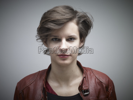 portrait of young woman against grey
