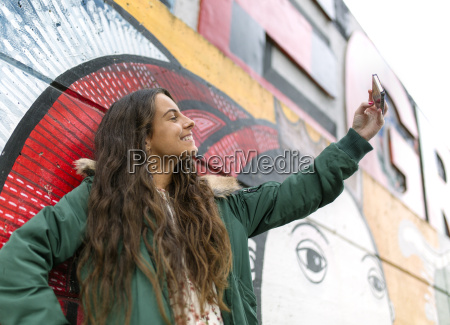 smiling young woman taking a selfie