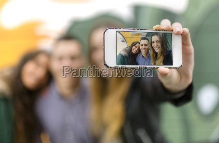 selfie of smiling friends on display