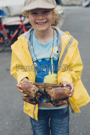 smiling boy holding great crab