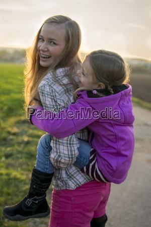 teenage girl carrying girl piggyback