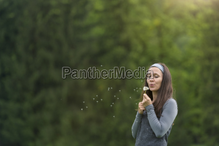 young woman blowing blowball in front