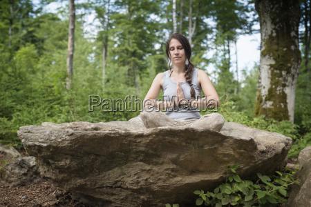 frau die auf felsen im meditierenden