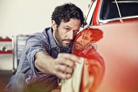 man polishing his vintage car