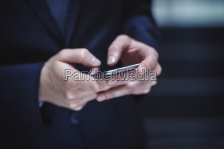 hands of businessman holding smartphone