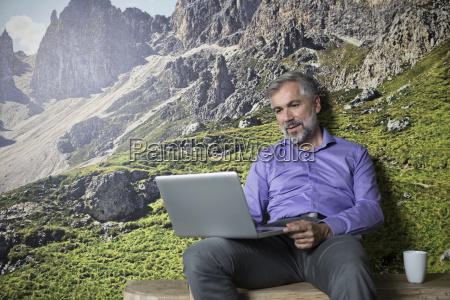 businessman using laptop sitting at photographic