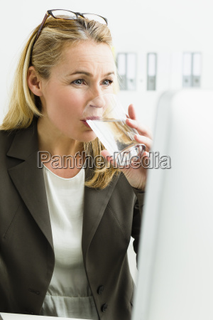 germany businesswoman drinking water and looking