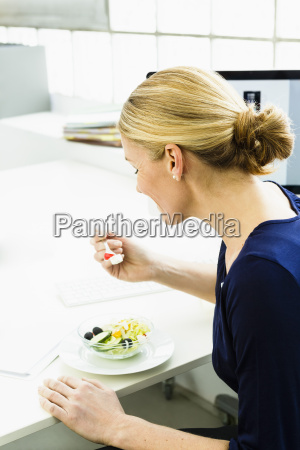 germany businesswoman eating salad smiling