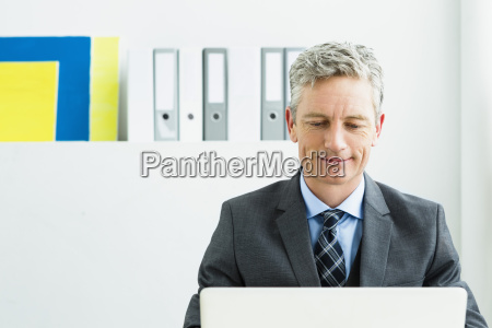 germany businessman using laptop in office