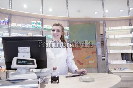 junger apotheker in der apotheke laechelnd