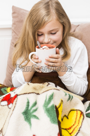 little girl holding cup of hot