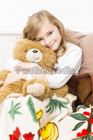 smiling little girl cuddling with her