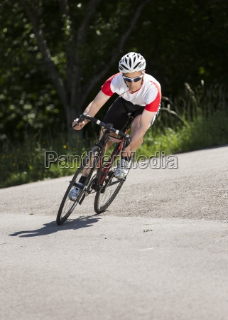 germany mature man riding bicycle on