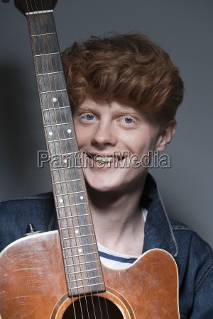 portrait of young man holding guitar