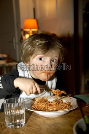 germany boy eating spaghetti close up