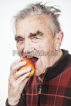 portrait of senior man eating apple