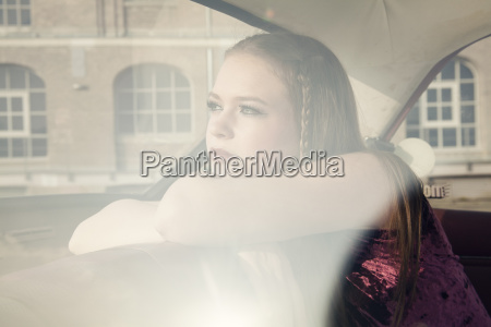 young woman looking through window of