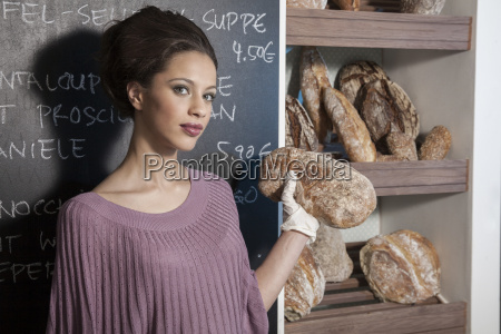 portrait of young woman holding bread