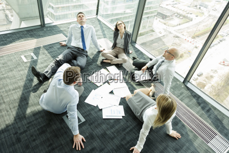 businesspeople sitting on floor looking up