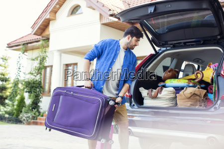 father packing car boot for family