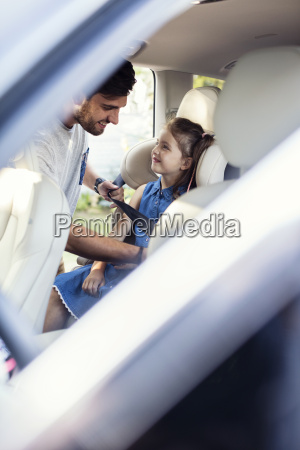 father fastening seat belt for daughter