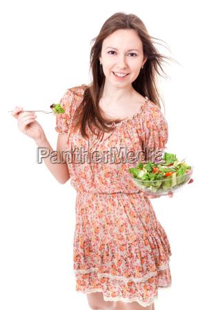 glueckliche junge frau isst salat