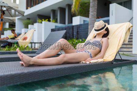 junge frau geniessen sonnenbad im schwimmbad