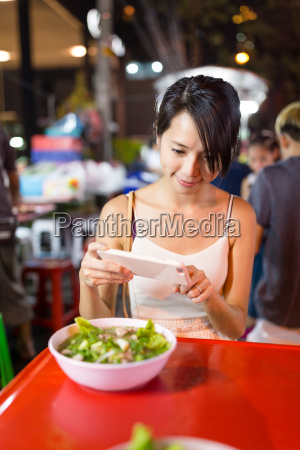 woman taking photo on her food