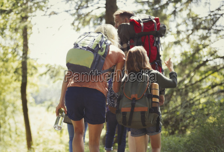 family with backpacks hiking in sunny