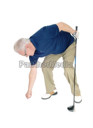 senior mann erfreut seinen golfball