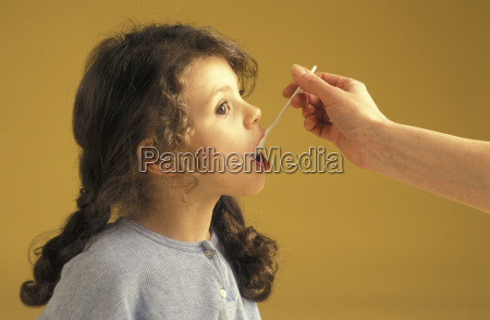 girl eating from spoon portrait