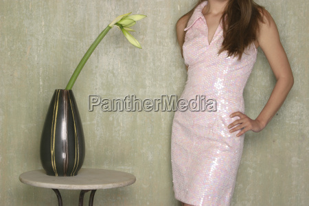 woman standing beside vase with flower