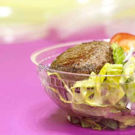 hamburger with mixed salad in plastic
