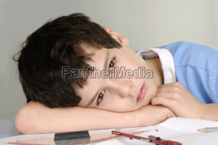 boy tired from doing his homework