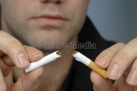 man breaking cigarette close up