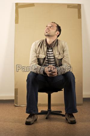 mann der vor dem karton sitzt
